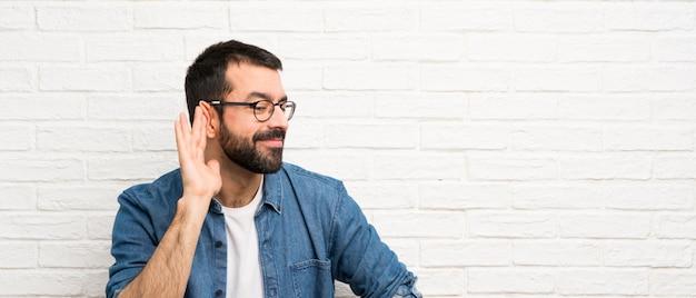 Bel homme à la barbe sur mur de briques blanches écouter quelque chose en mettant la main sur l'oreille
