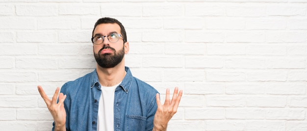 Bel homme à la barbe sur mur de briques blanches frustré par une mauvaise situation