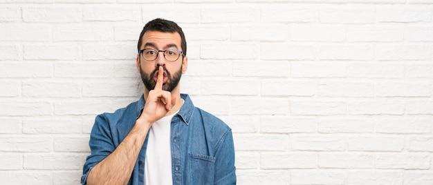 Bel homme à la barbe sur le mur de briques blanches montrant un geste du silence mettant le doigt dans la bouche