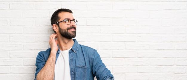 Bel homme à la barbe sur mur de briques blanches pense à une idée