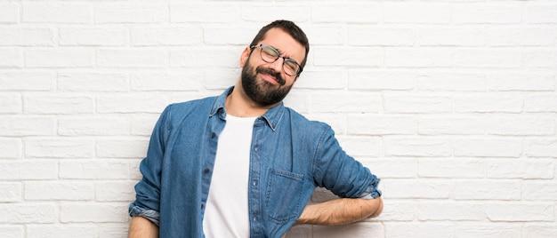 Bel homme à la barbe sur mur de briques blanches souffrant de maux de dos pour avoir fait un effort