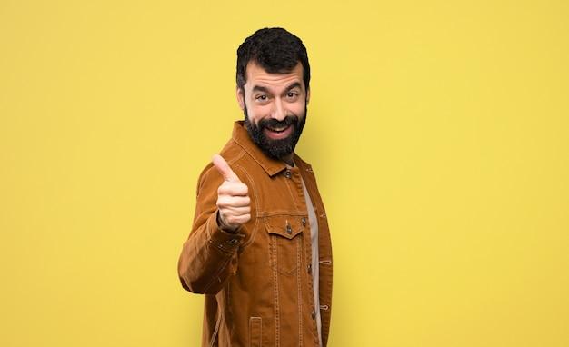 Bel homme à la barbe avec le pouce levé parce que quelque chose de bien est arrivé