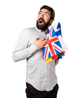 Bel homme à la barbe tenant beaucoup de drapeaux et amoureux