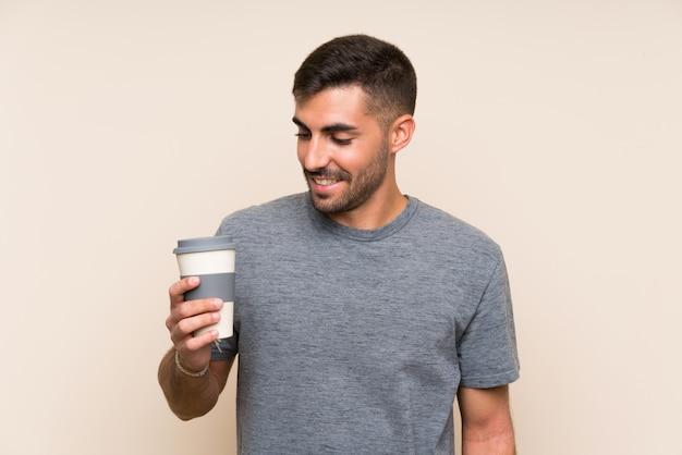 Bel homme à la barbe tenant un café à emporter sur un mur isolé souriant beaucoup