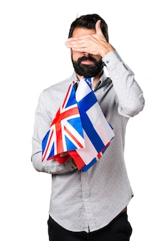 Un bel homme à la barbe tenant de nombreux drapeaux et couvrant ses yeux