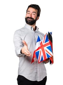 Un bel homme avec de la barbe tenant de nombreux drapeaux et faisant un accord