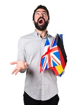 Un bel homme à la barbe tenant de nombreux drapeaux et faisant un geste de surprise