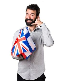 Un bel homme avec de la barbe tenant de nombreux drapeaux et faisant un geste téléphonique