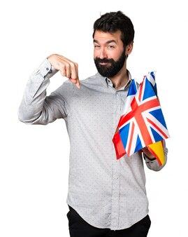 Un bel homme avec de la barbe tenant de nombreux drapeaux et pointant vers le bas