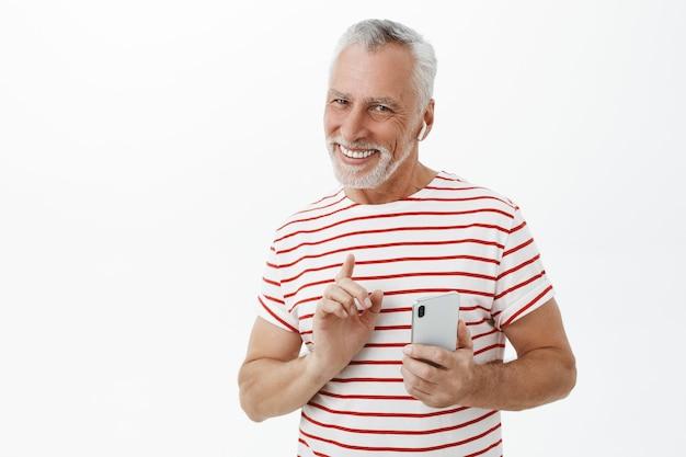 Bel homme barbu adulte souriant à l'aide d'écouteurs sans fil et smartphone