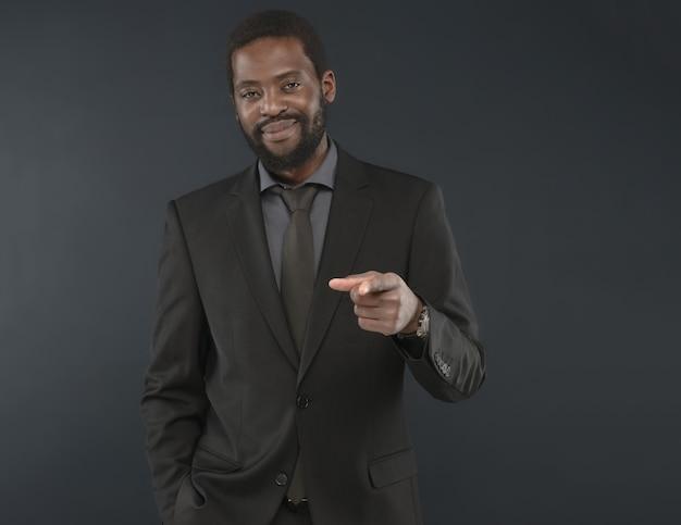 Bel homme barbu d'âge moyen avec le sourire sur le visage.homme vêtu d'un costume noir avec cravate pointe du doigt le spectateur. simbol de collaboration réussie concept d'attractivité masculine noire.