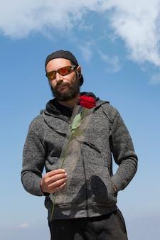 Bel homme barbu américain portant des lunettes de soleil, une casquette et une veste à capuche contre le ciel bleu. portrait d'un mec brutal de race blanche russe tenant une fleur rose rouge à la main. vacances romantiques et saint valentin
