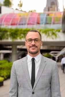 Bel homme barbu chauve hispanique avec des lunettes à l'extérieur d'un bâtiment moderne