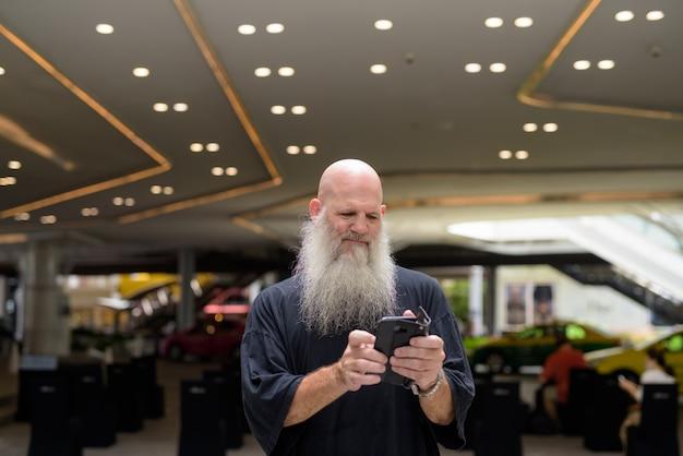 Bel homme barbu chauve mature à l'aide de téléphone dans la ville à l'extérieur