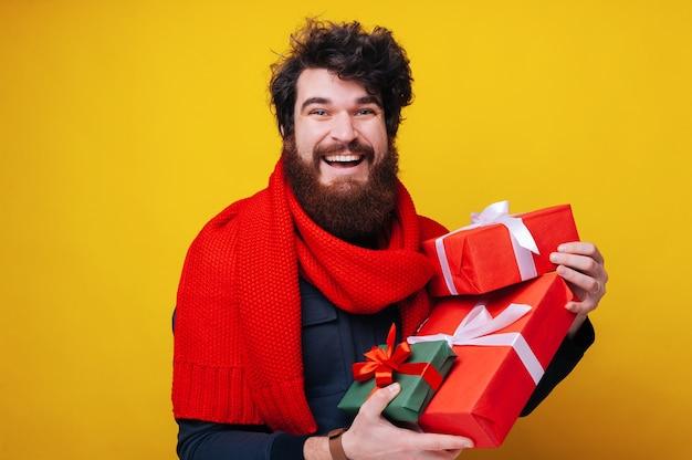 Bel homme barbu en écharpe rouge, tenant des coffrets cadeaux, concept de vente, profitant de cadeaux, fond jaune isolé