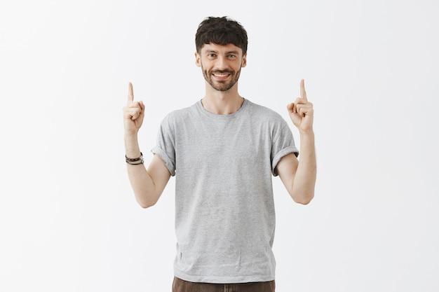 Bel homme barbu élégant pointant les doigts vers le haut et souriant heureux