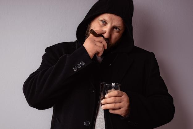 Un bel homme barbu élégant portant un manteau noir boit de l'alcool fort et fume son cigare