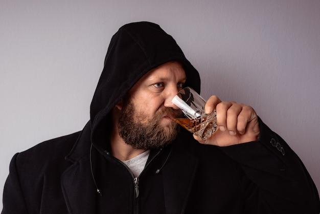 Bel homme barbu élégant portant un manteau noir avec capuche boisson avec de l'alcool fort