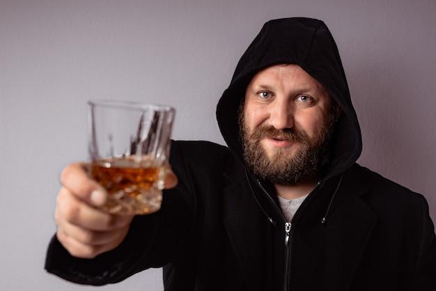 Bel homme barbu élégant portant un manteau noir avec capuche boisson et toast avec de l'alcool fort