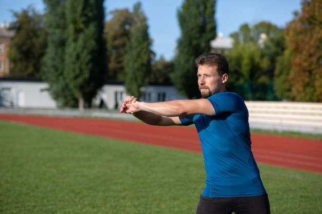Bel homme barbu faisant des bras se réchauffer avant de s'entraîner au stade. espace pour le texte