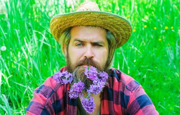Bel homme barbu avec des fleurs dans la barbe. homme à la barbe décorée.