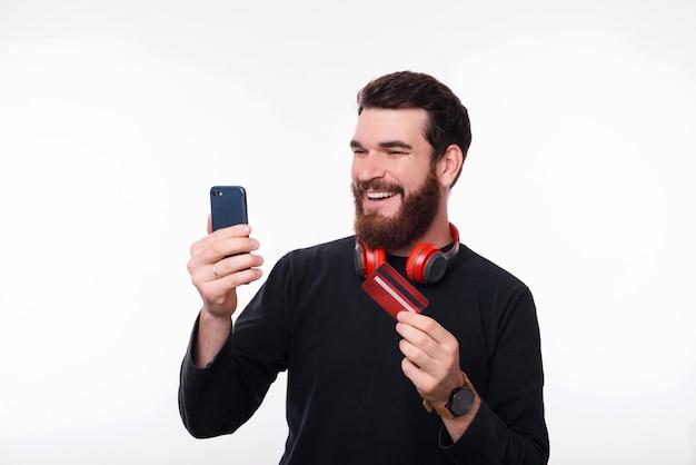 Bel homme barbu, gars hipster tenant sa carte de crédit et acheter de nouveaux gadgets en ligne à l'aide de smartphone