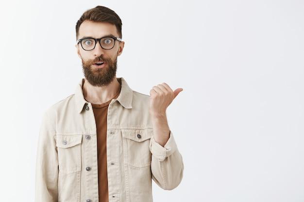 Bel homme barbu heureux dans des verres posant contre le mur blanc