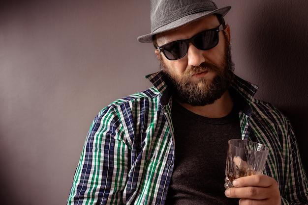 Un bel homme barbu hipster avec un chapeau, des lunettes de soleil et une chemise boit de l'alcool fort.
