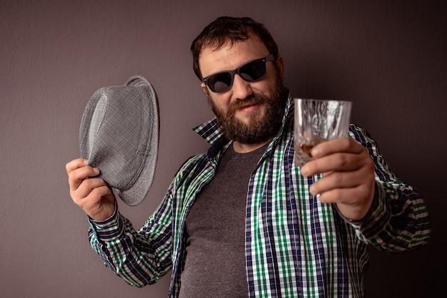 Bel homme barbu hipster avec des lunettes de soleil et une chemise, boire un toast à l'alcool fort et célébrer