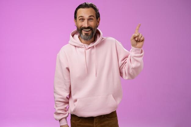 Bel homme barbu mature excité des années 40 rides les cheveux gris en riant joyeusement agissant immature s'amusant amusant voyage de vacances pointant vers le haut étonné souriant impressionné surpris, fond violet.