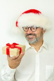 Bel homme barbu portant un chapeau de noël tenant une boîte-cadeau avec un ruban rouge