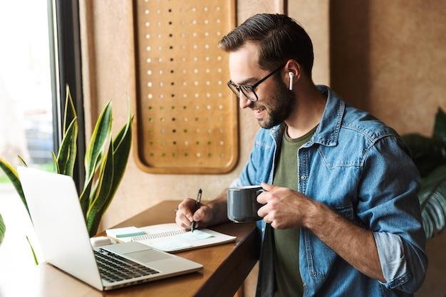 Bel homme barbu portant des lunettes écrivant des notes et buvant une tasse de thé tout en travaillant dans un café à l'intérieur