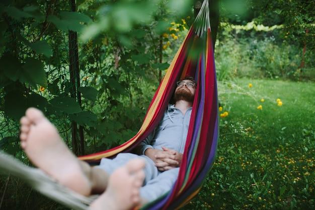 Bel homme barbu se détendre dans un hamac à l'ombre dans le jardin vert d'été
