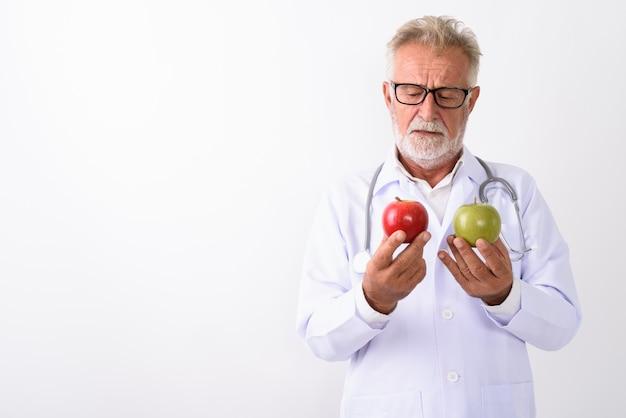 Bel homme barbu senior médecin choisissant entre pomme rouge et pomme verte sur blanc