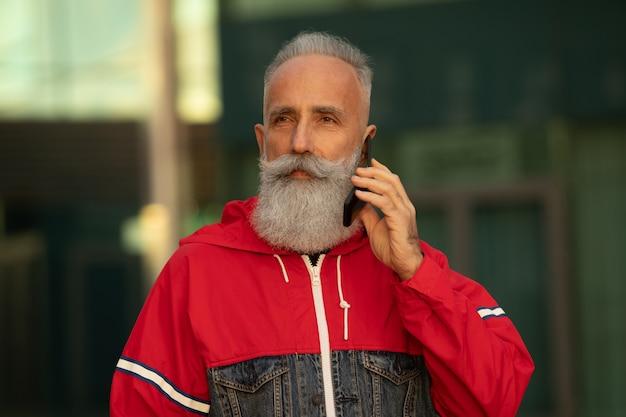 Bel homme barbu senior parle par un smartphone tout en prenant une pause-café dans une rue à côté de l'immeuble de bureaux.