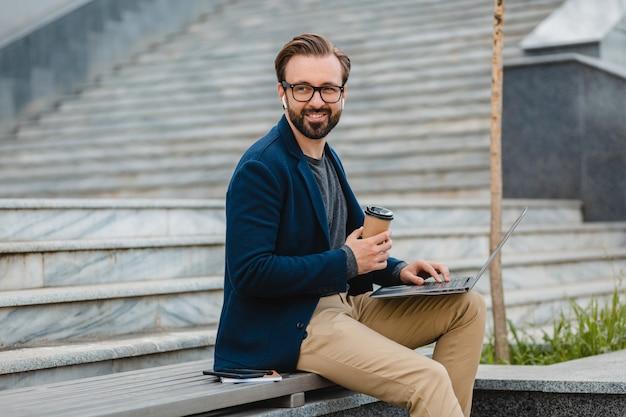 Bel homme barbu souriant dans des verres travaillant sur ordinateur portable
