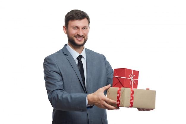Bel homme barbu souriant tenant des cadeaux présentant au spectateur posant sur fond de studio blanc.
