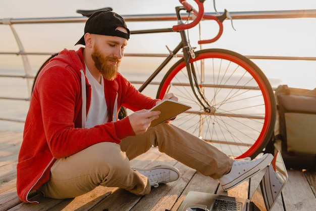 Bel homme barbu de style hipster travaillant en pigiste en ligne sur ordinateur portable avec sac à dos et vélo au lever du soleil du matin au bord de la mer, voyageur de mode de vie actif sain