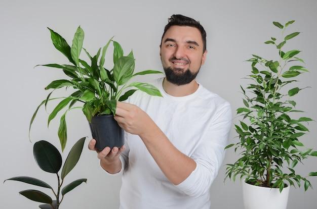 Bel homme barbu tenant une plante d'intérieur avec pot de lys de la paix dans les mains et souriant