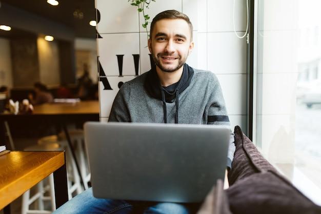 Bel homme barbu travaille sur un ordinateur portable alors qu'il était assis au café