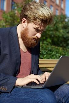 Bel homme barbu travaille sur un ordinateur portable à l'extérieur