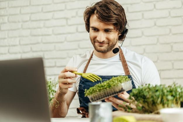 Bel homme barbu vend des pousses de plantes et des semis en ligne à l'aide d'un ordinateur portable