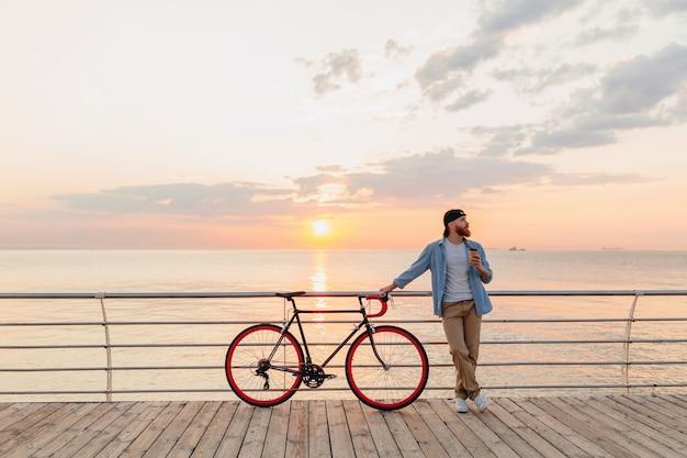 Bel homme barbu voyageant à vélo au lever du soleil du matin au bord de la mer, boire du café, voyageur de mode de vie actif sain