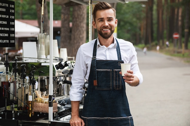Bel homme barista pendant le travail dans son café de la rue mobile