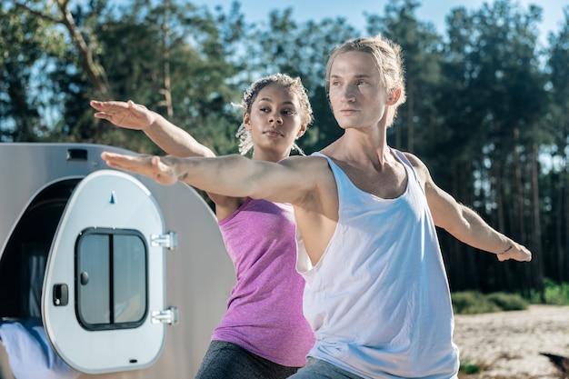 Bel homme. bel homme athlétique se sentir détendu tout en faisant du yoga avec sa petite amie mince à l'extérieur