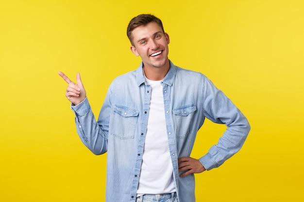 Bel homme blond adulte charismatique avec un sourire blanc parfait, introduire un nouveau produit, pointer le doigt dans le coin supérieur gauche, démontrer une bannière publicitaire, fond jaune debout