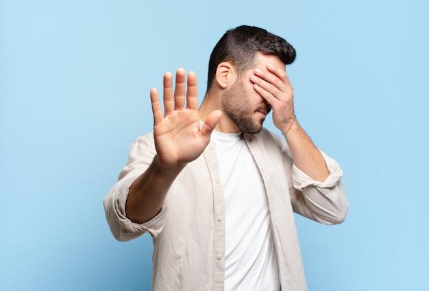 Bel homme blond adulte couvrant le visage avec la main et mettant l'autre main devant pour arrêter la caméra, refusant des photos ou des images