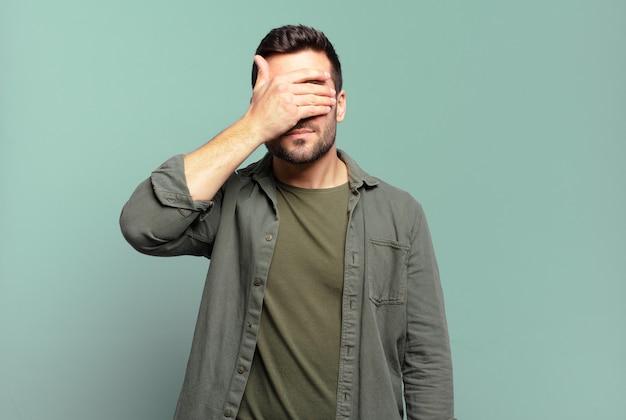 Bel homme blond adulte couvrant les yeux d'une main se sentant effrayé ou anxieux, se demandant ou attendant aveuglément une surprise