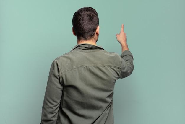 Bel homme blond adulte debout et pointant vers l'objet sur l'espace de copie, vue arrière