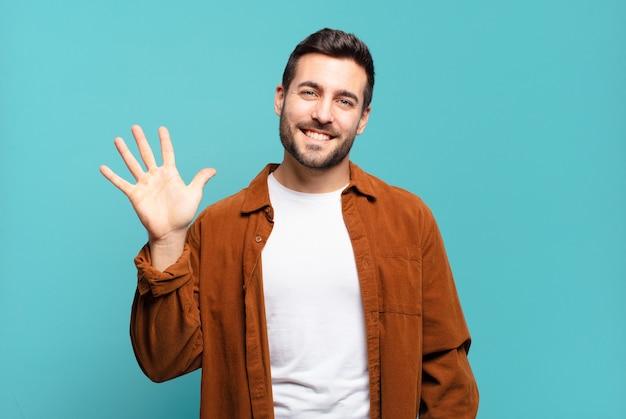 Bel homme blond adulte souriant et à la recherche amicale, montrant le numéro cinq ou cinquième avec la main en avant, compte à rebours